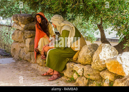A young man and woman in period costume in the open air museum of Nazareth Village Israel. This site provides a look at  ancient Israel - Stock Image