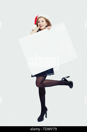 Surprised woman in black tights, high heels shoes and Santa hat holding empty paper banner card and standing on white background - Stock Image