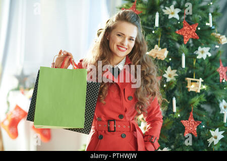 Portrait of smiling young woman in red trench coat near Christmas tree showing shopping bags - Stock Image