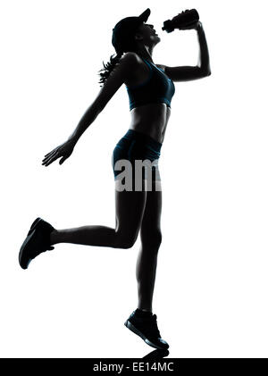 one caucasian woman runner jogger drinking in silhouette studio isolated on white background - Stock Image