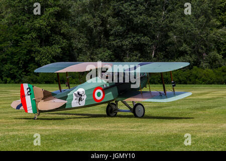 Biplane Spad S XIII replica from first world war on a meadow. - Stock Image