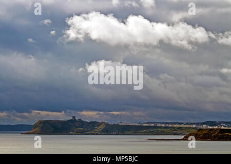 Scarborough's Castle headland and North Bay under stormy skies, seen from across the bay at Long Nab. - Stock Image