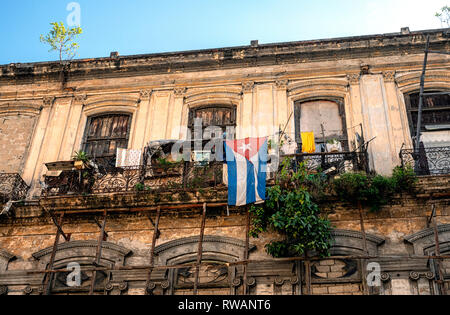 A Cuban flag hangs from the dilapidated balcony of a building in central Havana, capital of Cuba - Stock Image