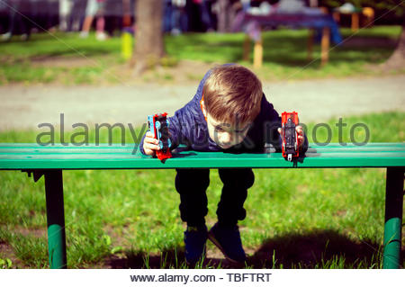Young boy laying on a wooden bench and holding two - Stock Image