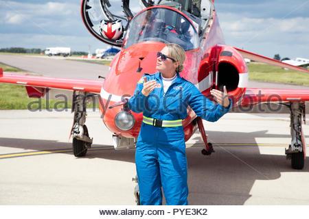Woman gesturing by Red Arrows airplane on RAF Scrampton, UK - Stock Image