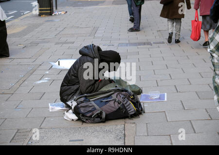 A homeless man dressed in black winter clothing sitting on the pavement sidewalk with head bowed and people walking by in London UK  KATHY DEWITT - Stock Image