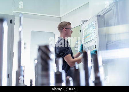 Apprentice engineer at controls of CNC machine in gearbox factory - Stock Image