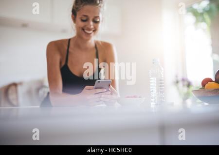 Smiling young woman having breakfast and using cell phone in the kitchen. Focus on mobile phone in female hands. - Stock Image
