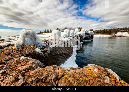 Waves from an early spring storm coat the shoreline of Gooseberry Falls State Park in a layer of ice. - Stock Image