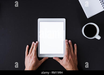 A top view of male hands holding tablet on a desk. Copy space. - Stock Image