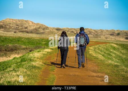 Hikers on the Norfolk Coast path National Trail near Barnham Overy Staithe, East Anglia, England, UK. - Stock Image