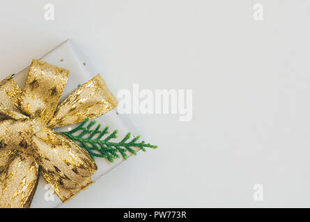 Elegant Gift Box Wrapped in Grey Silver Paper with Polka Dots Golden Ribbon Bow Juniper Twig. Christmas New Years Presents Shopping Sale. White Backgr - Stock Image