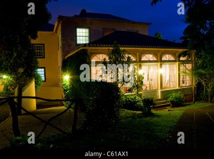 Exterior of Casa Velha Restaurant illuminated by night at Casa Velha do Palheiro Country House Hotel near Funchal, - Stock Image