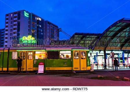 Poznan, Poland - November 16, 2018: Tram with Caffe Bimba on the Rataje bus station by night. - Stock Image