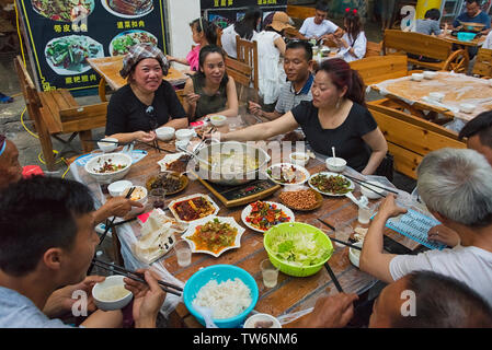 People dining on the street, Zhenyuan, Guizhou Province, China - Stock Image