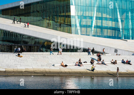 Oslo Opera House, waterfront view in summer of people sunbathing or walking on the vast access ramp leading to the roof of the Oslo Opera House. - Stock Image
