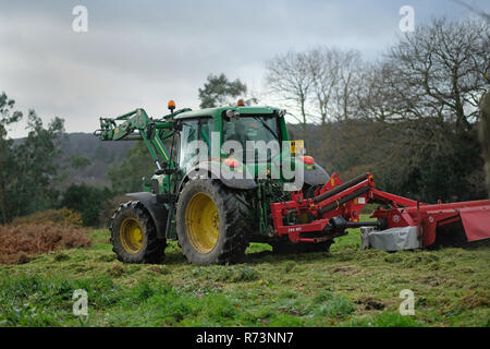A farm vehicle, tractor working in a field. - Stock Image