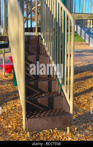 Metal brown stairs with yellow railing part from a children`s play area in a local park in Pitt Meadows, British Columbia, Canada. - Stock Image