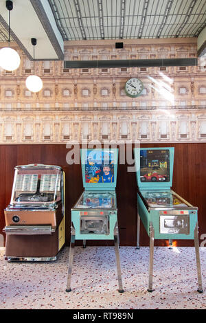 Pinball machines, juke box and retro wallpaper at Bar Luce, Wes Anderson-inspired bar and cafe in the Fondazione Prada district of Milan, Italy - Stock Image