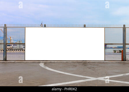 A blank billboard ready for new advertising on the harbor fence, big copy space - Stock Image