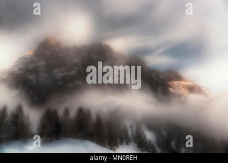 Fog around the mountain Sella with last rays of Sun on the top in winter season and woods in foreground, Dolomites - Italy - Stock Image