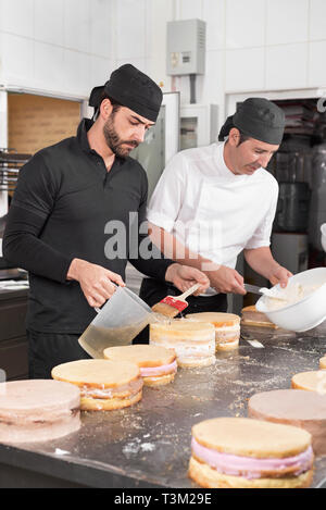 Two man pastry chefs working together making cakes at the pastry shop . - Stock Image