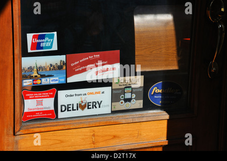 Stickers on store door - Stock Image