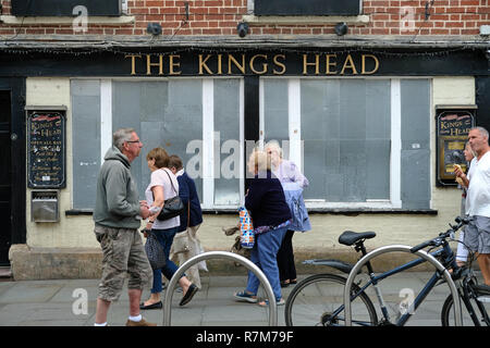 People walking past a boarded up public house. - Stock Image