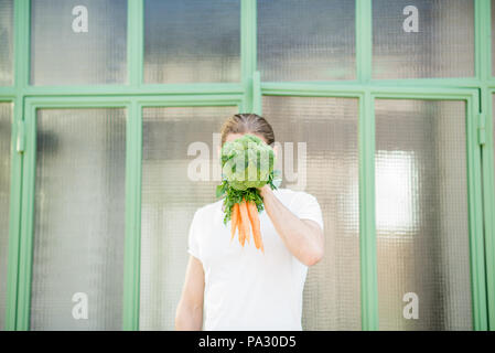 Funny portrait of a man holding broccoli with carrot instead of his head outdoors. Healthy eating concept - Stock Image