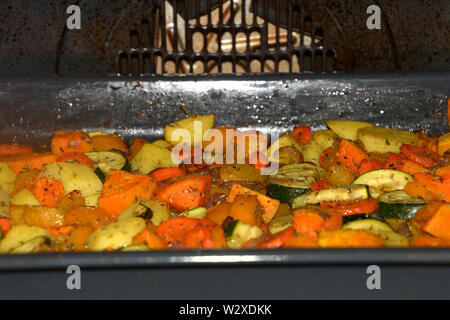baked oven vegetables, crispy grilled vegetarian and vegan oven vegetables seasoned with herbs and olive oil - Stock Image
