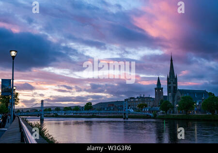 Dramatic colourful pink sunset at dusk over River Ness,with Greig Street footbridge, Inverness, Scotland, UK - Stock Image