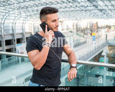 Young man in train station calling on cellphone - Stock Image