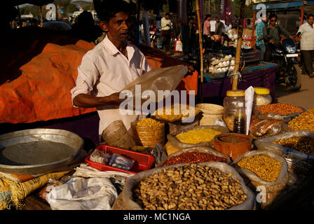 Street food stall in open market salesman selling variety of spicy nuts like peanuts groundnuts chickpeas and grams Bengal Gram Green Gram red grams - Stock Image
