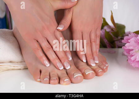 Girl hands and bare feet with french manicure and pedicure nails polish on white towel in beauty salon and decorative pink flowers in background - Stock Image