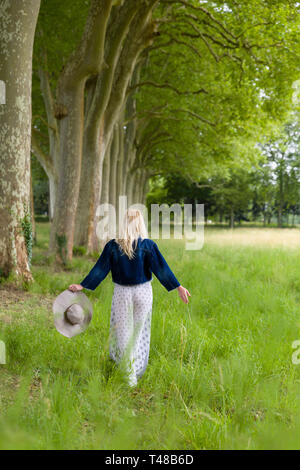 Beautiful young blonde woman walking in the countryside in summertime - Stock Image