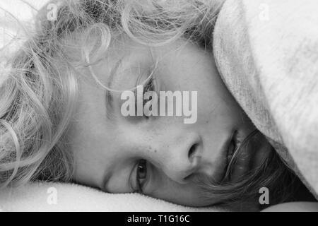 Black and white portrait of a lethargic girl waking up - Stock Image