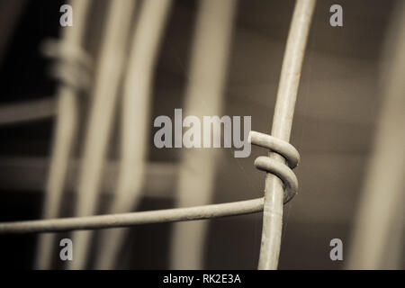Abstract detail of metal wires connected by hook. Sad melancholy background in brown tone. Old wire mesh close-up. Idea of connection and cohesion. - Stock Image