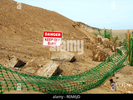 An attempt to protect the face of a sand dune from further marine erosion by regrading of the slope and provision of basic rock armour, Winterton, Nfk. - Stock Image