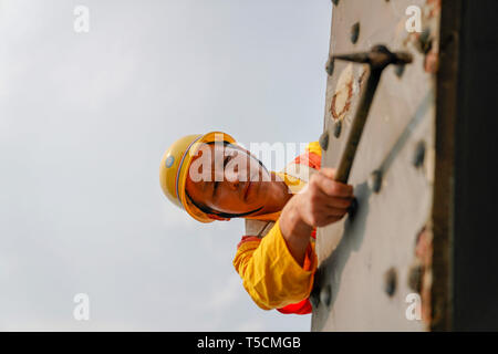 (190423) -- CHONGQING, April 23, 2019 (Xinhua) -- Tang Jinhua checks rust on the previous Baishatuo Yangtze River railway bridge in Jiangjin of southwest China's Chongqing Municipality, April 23, 2019. The previous Baishatuo Yangtze River railway bridge, completed in 1959, will stop service after April 24. All trains will run on the new double decker steel truss cable stay railway bridge after that day. The new bridge has 4 tracks on the upper deck for passenger trains with a designed speed of 200 kilometers per hour and 2 tracks on the lower deck for cargo trains with the designed speed of 12 - Stock Image