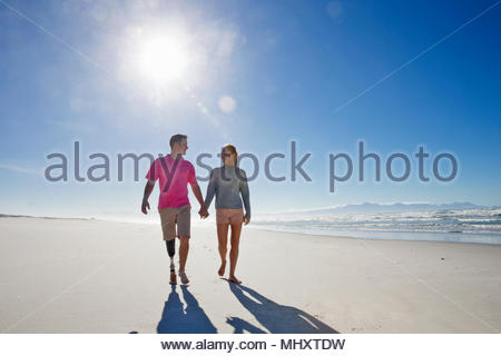 Front View Of Man With Artificial Leg Walking Along Beach Holding Hands With Female Partner On Summer Vacation - Stock Image