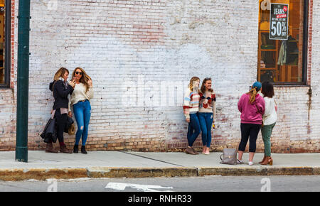 ASHEVILLE, NC, USA-2/16/19: Young women taking turns posing for impromptu smart phone pictures, with white brick wall as background. - Stock Image
