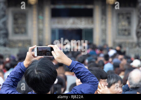 Taipei, Taiwan, Feb. 5, 2019: A man takes a picture with his mobile phone as he enters Longshan Temple in Taipei on Tuesday, Lunar New Year's Day and the first day of the Year of the Pig. Credit: Perry Svensson/Alamy Live News - Stock Image