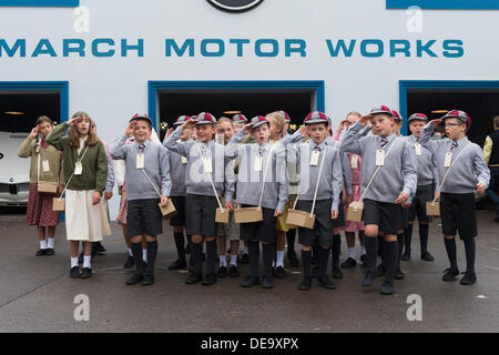 Chichester, West Sussex, UK. 13th Sep, 2013. Goodwood Revival. Goodwood Racing Circuit, West Sussex - Friday 13th September. Children outside the March Motor Works facade perform a war time song dressed in school uniform and gas mask boxes. © MeonStock/Alamy Live News - Stock Image