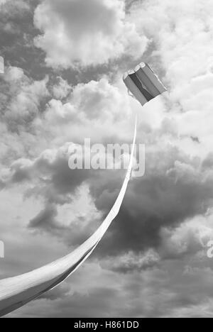 kite under cloudy sky with lightning - Stock Image