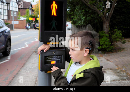 A young boy 8 walking to school waiting to cross the road at a pedestrian traffic lights crossing sign in an urban area UK  KATHY DEWITT - Stock Image