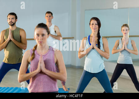 Group of people performing yoga - Stock Image