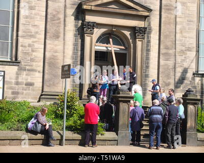 A church Easter procession with crown of people carrying large wooden crucifix on Good Friday in the town of Hebden Bridge, Calderdale, UK - Stock Image