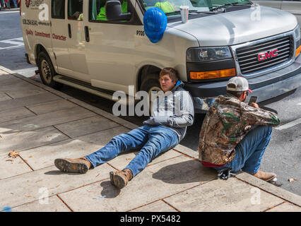 ASHEVILLE, NC, USA-10/17/18: Two young male plumbers taking a break on the sidewalk. - Stock Image