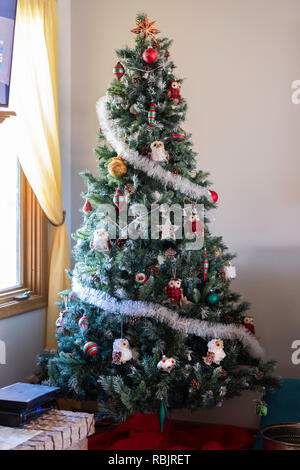 An artificial Christmas tree decorated with owl ornaments and balls standing in the corner of a home. USA - Stock Image