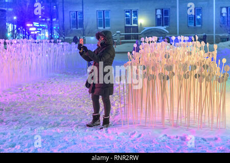 Young woman taking a selfie photo in downtown Calgary during the Glow Downtown Winter Light Festival - Stock Image